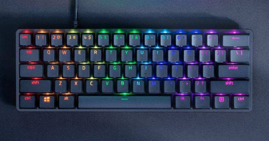 Illuminated view of gaming Razer Huntsman Mini keyboard on black desk mat