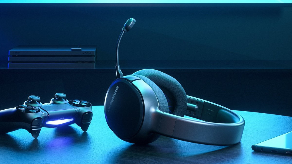 The Arctis wireless headphones between a ps4 controller and an android phone bathed in blue light