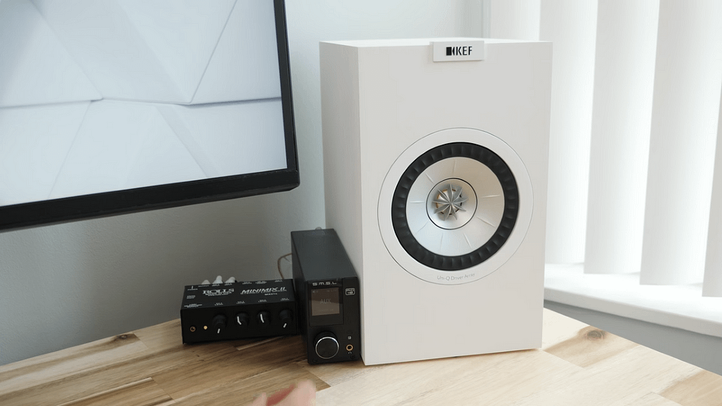 A single white KEF Q150 bookshelf speaker sitting on a light desk next to audio equipment
