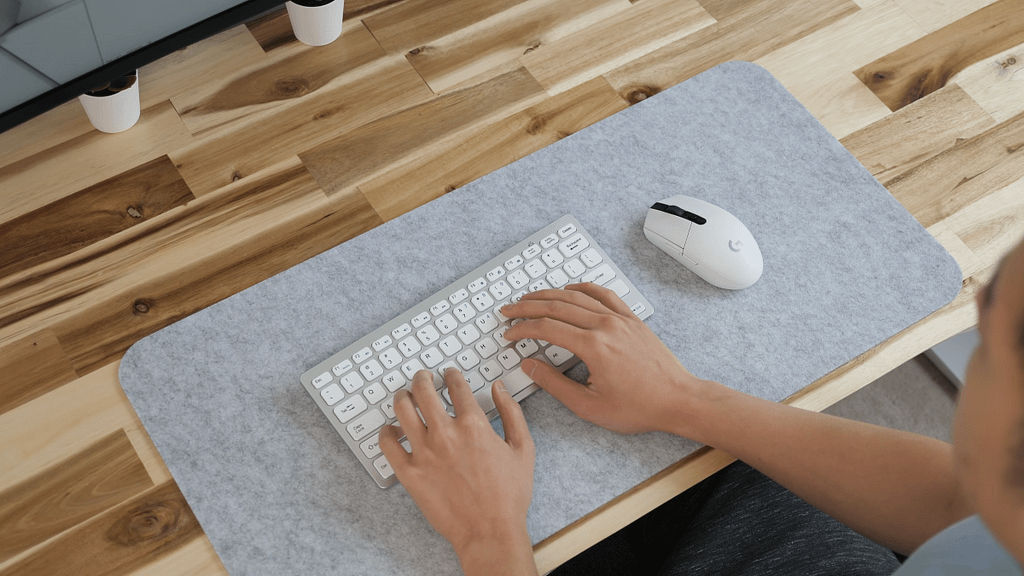 White Logitech G305 next to a white and silver small form factor keyboard on a grey mat