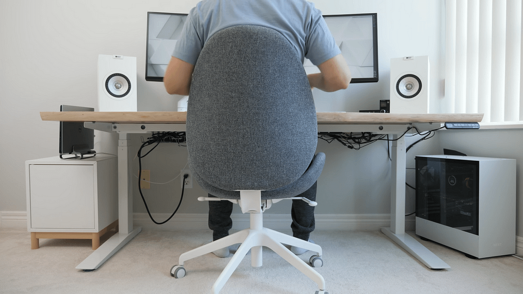 White base IKEA Gunnared chair with grey fabric in front of minimalist home office design