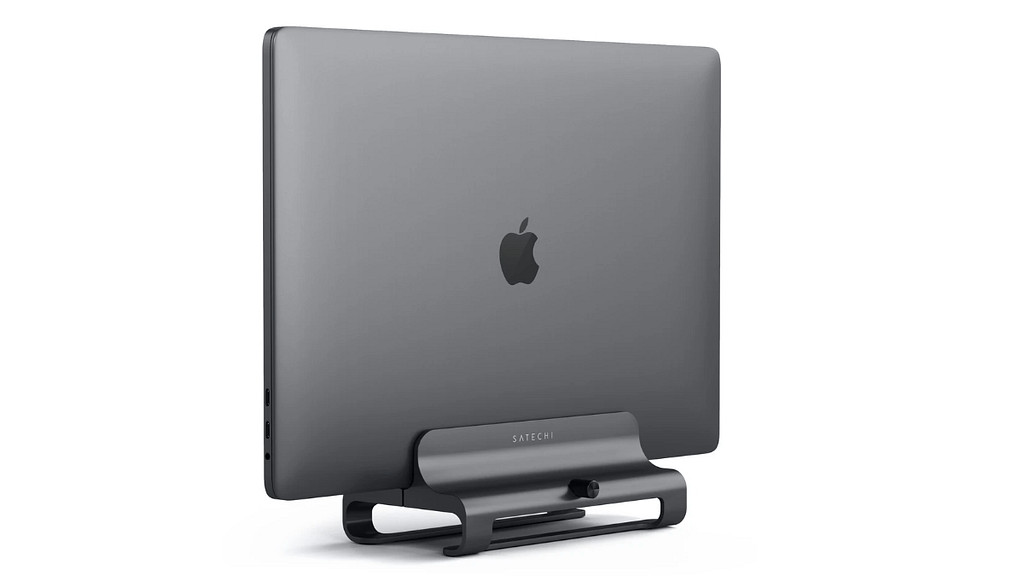 An Apple laptop held vertically by the aluminum Satechi Laptop stand against a plain background