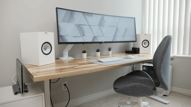 A minimalist home office setup against on a natural wood desk against a white background