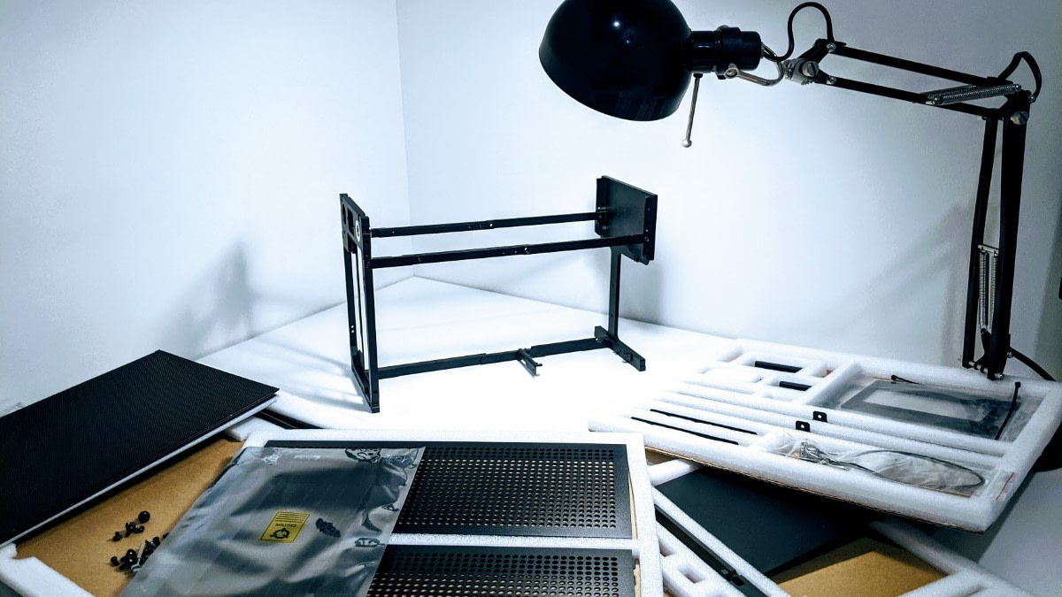Wide view of partially assembled Formd T1 in the corner of a desk surrounded by computer parts, illuminated by a black lamp